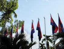 A row of flagpoles with flags of Cambodia on the background of a clear sky. Windless sunny day stock photo