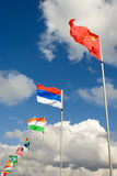 Row of flags. Row Of international Flags on the metal poles and sky at background Royalty Free Stock Photography