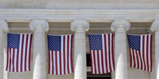 Row of Flags. Old Greek Revival architecture court house with flags hanging between its columns Royalty Free Stock Images