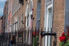 Row of Flats. Dublin, Ireland -- July 9, 2018. A red haired woman is sitting on the stoop of a flat that is part of a row of flats in Dublin, Ireland stock photo
