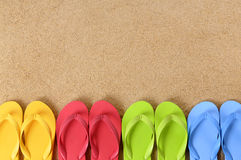Flip flops row summer beach background border copy space. Flip flops in a row on a sandy beach. Space for copy royalty free stock photography