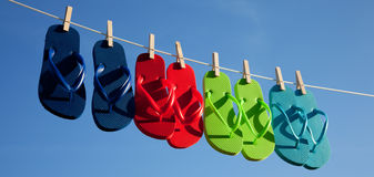Row of flipflops against a blue sky Stock Image