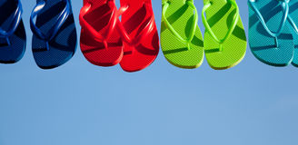 Row of flipflops against a blue sky Stock Photos