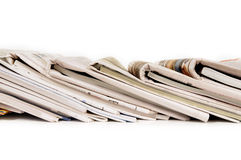 Row of folded newspapers, stacked leaning, isolated on white background Stock Photography