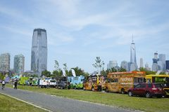 A row of food trucks in park for independence day. Manhattan skyline WTC in background. A row of food trucks in park for independence day. Manhattan skyline WTC Stock Photography
