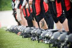 Row of football helmets and feet. On grass, selective focus Stock Photography