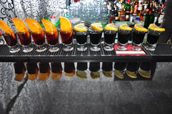 Row of four drinks of black vodka on the bar. Row of different shots of alcoholic drinks standing on the bar Royalty Free Stock Photos