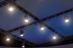 A row of four light projectors on a scene ceiling with cables and metal supports. Royalty Free Stock Photo
