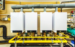 A row of four powerful domestic gas boilers.  royalty free stock photography