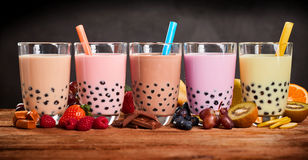 Row of fresh boba bubble tea glasses on wooden background stock images