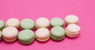 Row of fresh and delicious macaroons dessert. On pink background in studio stock video