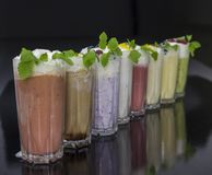 Row of fresh milk cocktails with fruits and berries. On black background Stock Image