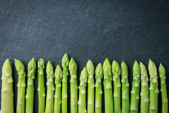 Row of fresh raw green Asparagus on dark stone background. Organ. Ics fresh green vegetable Garden Asparagus background Stock Photography
