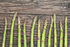 Row of fresh raw green Asparagus on wooden table. Row of fresh raw green Asparagus on wooden Stock Photo