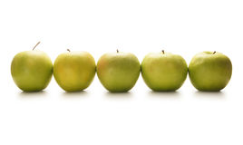 A row of fresh and tasty green apples on white Stock Image