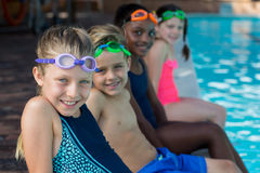 Row of friends sitting at pool side. Portrait of friends sitting at pool side Royalty Free Stock Photo