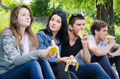Row of friends sitting together. Row of young college friends sitting together watching an event with focus to the middle couple Royalty Free Stock Photo