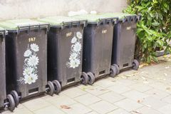 Row of garbage containers, some decorated to make them beautiful, in the city against an old cement wall. A green plant next to th royalty free stock images