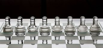 Row of glass chess pawns on a board with black and white shade stock photo