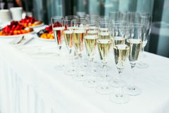 A row of glasses filled with champagne are lined up ready to be Stock Photography