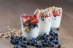 The row of the glasses full of yogurt, berrie and cereal and. The row of three glasses full of yogurt, berrie and cereal and blueberries on the wooden table stock images
