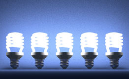 Row of glowing spiral light bulbs on blue Royalty Free Stock Images