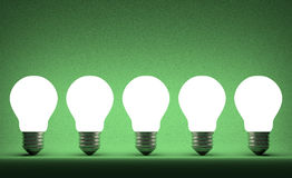 Row of glowing tungsten light bulbs on green Stock Photo