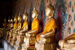 A row of golden Buddhas Stock Photo