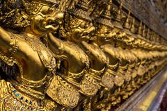 Row of golden garuda figures, Temple of the Emerald Buddha, Grand Palace, Bangkok, Thailand royalty free stock images