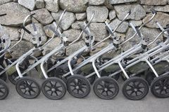 Row of golf pull carts. A row of metal push pull golf carts lined up and ready to go golfing stock photos