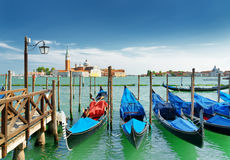 A row of gondolas parked at pier beside the Riva degli Schiavoni Royalty Free Stock Image