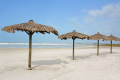 Row of Grass Beach Cabanas by the Ocean Royalty Free Stock Photos