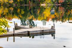 Row of Green Adirondack Chairs on a Jetty Stock Photography