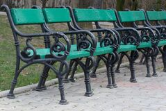 row-of-green-benches-on-alley Royalty Free Stock Photos