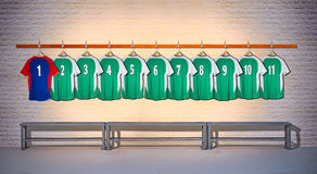 Row of Green and Blue Football shirts Shirts 1-11. Hanging on Locker room wall stock photo
