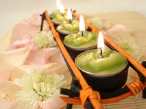 Row of green candles over straw matt with rose petals stock photo