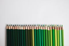 Row of green coloured pencils lying one to another in a line. D. Ifferent shades of green. Concept of taking care of ecology and environment royalty free stock image