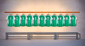 Row of Green and Football shirts Shirts 1-11. Row of Green and Red Football shirts Shirts 1-11 hanging on locker room wall royalty free stock image