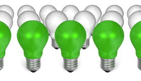 Row of green light bulbs in front of white ones Royalty Free Stock Image