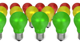 Row of green light bulbs in front of yellow and red ones Royalty Free Stock Images