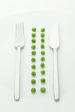 Row of green peas with fork and knife Stock Photo