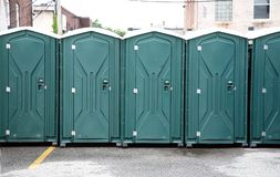 Row of Green Portable Toilets. This row of gree portable toilets at an outside event royalty free stock image
