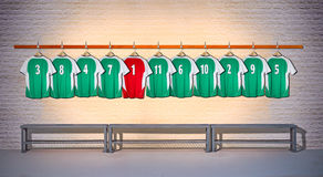 Row of Green and Red Football shirts 3-5. Row of Green and Red football shirts on hangers in Locker room stock photos