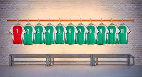 Row of Green and Red Football shirts Shirts 1-11. Hanging on locker room wall royalty free stock image
