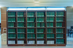 Row of green thesis in the large bookshelf in Chulalongkorn univ stock image