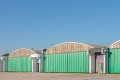 Row of green warehouses with rounded rooftops Stock Photo