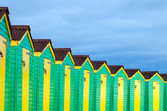 Row of Green and Yellow Beach Huts Royalty Free Stock Images