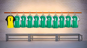 Row of Green and Yellow Football shirts Shirts 1-11. Hanging on locker room wall stock photos