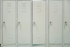 A row of grey metal school lockers with keys in the doors.  stock photography