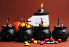 Row of Halloween Trick or Treat witches cauldrons full of candy Stock Photo